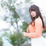 傘を差してこっちをみる女性