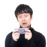 スマートフォンを見てびっくり顔の男性