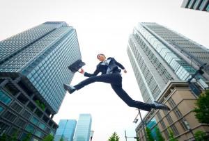 ビル街を飛び跳ねる男性