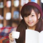 本を片手にお茶をしている女性