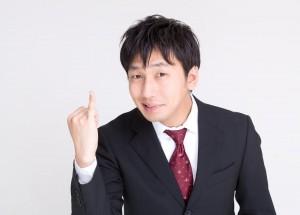 小指を立てるスーツの男性