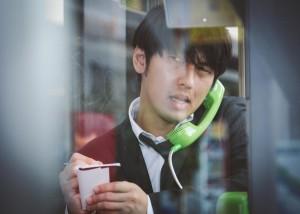 電話ボックスでメモをとる男性