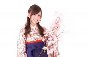 桜の枝と袴姿の女性