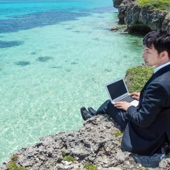 崖でパソコンを使う男性