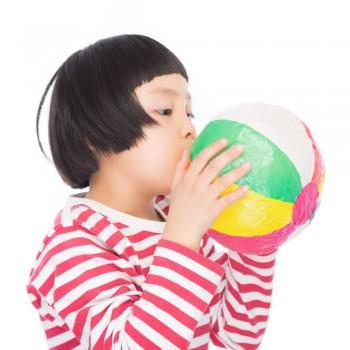 紙風船を膨らませる子ども
