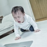パソコンを前に泣く赤ちゃん