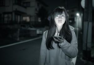 暗闇でスマホを操作する女性