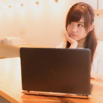 パソコンを前に悩む女性