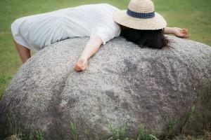 石の上に寝転がる女性
