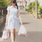 買い物袋を持って歩く女性