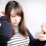 スマホカメラを鏡代わりにする女性