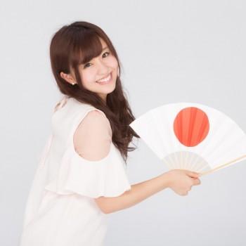 日の丸の扇子を広げる女性