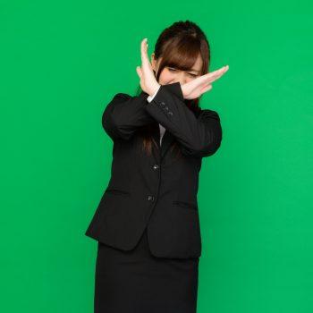 手で拒否を示すスーツ女性