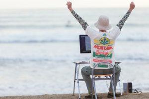 浜辺でパソコン作業を終えた男性