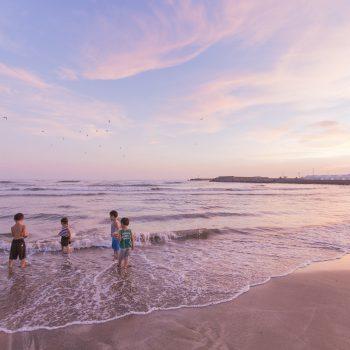 夕暮れ時に浜辺で遊ぶ子ども