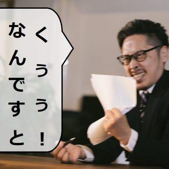 紙をぐしゃぐしゃにして「なんですとぉ?!」と憤慨する男性
